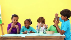 Cute pupils painting eggs for easter. At the elementary school stock footage