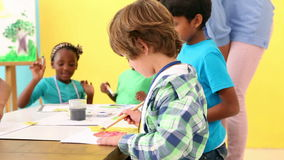Cute pupils painting pictures with teacher. At the elementary school stock video footage