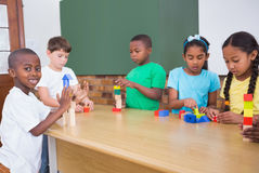 Cute pupils playing with building blocks Stock Photos