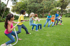 Cute pupils playing tug of war on the grass outside Royalty Free Stock Images
