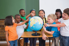 Cute pupils pointing to globe in classroom Stock Photo