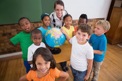 Cute pupils pointing to globe in classroom Stock Photography