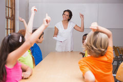 Cute pupils raising their hands in class Royalty Free Stock Image