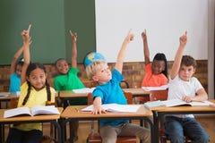 Cute pupils raising their hands Stock Photos