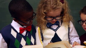 Cute pupils reading books. In classroom at the elementary school stock footage