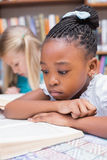Cute pupils reading books in library Royalty Free Stock Photo