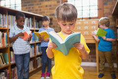 Cute pupils reading books at library Royalty Free Stock Photo