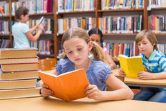 Cute pupils reading in library Royalty Free Stock Image