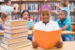 Cute pupils reading in library Stock Photos