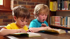 Cute pupils reading in library. At elementary school stock video