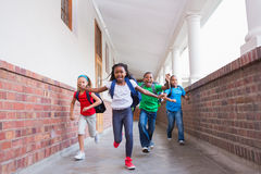 Cute pupils running and smiling at camera in hallway Stock Photo