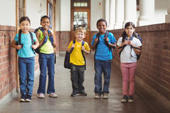 Cute pupils with schoolbags standing at corridor Stock Image