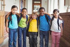 Cute pupils with schoolbags standing at corridor Royalty Free Stock Photography