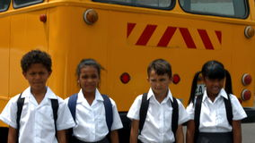 Cute pupils showing thumbs up by bus stock video footage