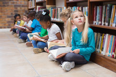 Cute pupils sitting on floor in library Royalty Free Stock Image