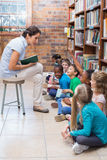 Cute pupils sitting on floor in library Royalty Free Stock Photos