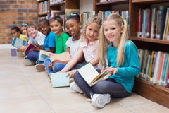 Cute pupils sitting on floor in library Royalty Free Stock Images