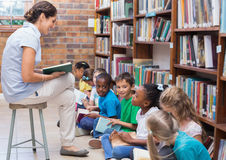 Cute pupils sitting on floor in library Royalty Free Stock Photo