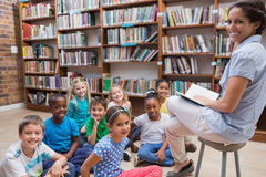Cute pupils sitting on floor in library Royalty Free Stock Photography