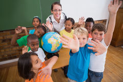 Cute pupils smiling around a globe in classroom with teacher Royalty Free Stock Photos