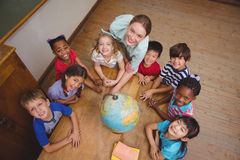 Cute pupils smiling around a globe in classroom with teacher Royalty Free Stock Images