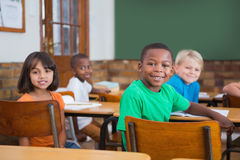 Cute pupils smiling at camera in classroom Stock Photos