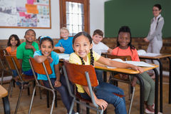 Cute pupils smiling at camera in classroom Stock Images