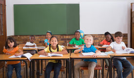 Cute pupils smiling at camera in classroom Royalty Free Stock Images