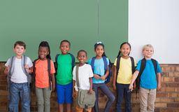 Cute pupils smiling at camera in classroom Stock Photography
