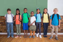Cute pupils smiling at camera in classroom Royalty Free Stock Image