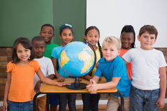 Cute pupils smiling at camera in classroom with globe Royalty Free Stock Photos