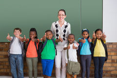 Cute pupils smiling at camera in classroom showing thumbs up Royalty Free Stock Images
