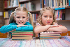 Cute pupils smiling at camera in library Royalty Free Stock Photos