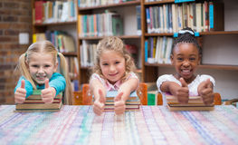 Cute pupils smiling at camera in library Royalty Free Stock Image