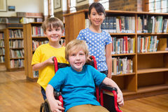Cute pupils smiling at camera at the library Stock Images
