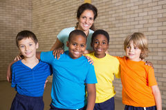Cute pupils smiling at camera with PE teacher Royalty Free Stock Image