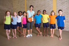 Cute pupils smiling at camera with PE teacher Royalty Free Stock Photography