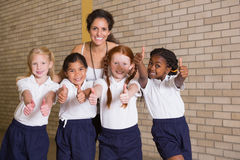 Cute pupils smiling at camera in PE uniform Stock Photography