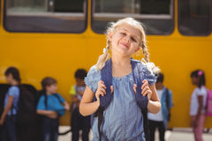 Cute pupils smiling at camera by the school bus Royalty Free Stock Images