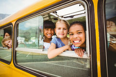 Cute pupils smiling at camera in the school bus Royalty Free Stock Photography