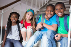Cute pupils smiling at camera on the stairs Stock Image