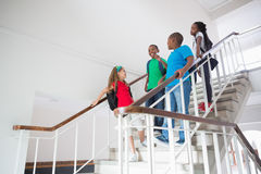 Cute pupils smiling and walking down stairs Stock Photo