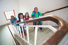 Cute pupils smiling and walking up stairs Royalty Free Stock Image