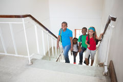 Cute pupils smiling and walking up stairs. At the elementary school Stock Photography