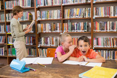 Cute pupils speaking at library Royalty Free Stock Images