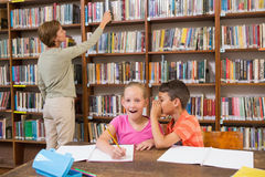 Cute pupils speaking at library Royalty Free Stock Image