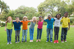 Cute pupils standing on the grass outside Royalty Free Stock Photo