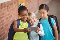 Cute pupils taking selfies at corridor Stock Images