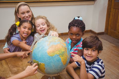 Cute pupils and teacher in classroom with globe Stock Photos