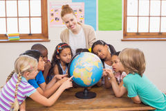 Cute pupils and teacher in classroom with globe Royalty Free Stock Photos